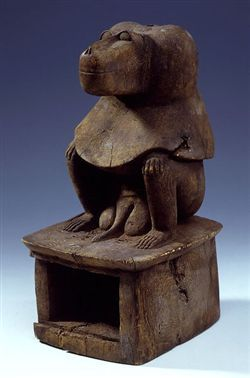 This figure of the god Thoth is shaped as a baboon seated on a high pedestal. The pedestal is hollow and is closed at the front by a sliding panel. The baboon has been distinctly modelled with its thick muzzle and its hairy mantle. The genitals have been rendered overly large in comparison with the minute hands and feet.