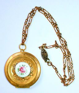 "A sweet guilloche with painted rose sits upon a raised platform surrounded by reticulated petals. Floral repousse design on back. Circa 1920s. Chain, 8.5"" hooked; locket, 1.5"" diameter. Unmarked Appears gold/gold-filled. $65"