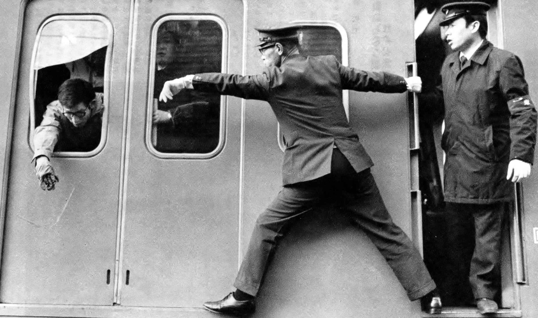 シリを押せば手が出る。1月朝の新宿駅は「着ぶくれラッシュ」の名所。シリ押しで詰め込まれた反動で、反対側のガラスが破れ手が出る始末。1971年読売報道写真集より。