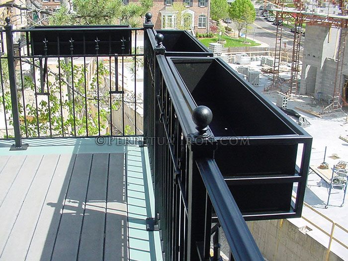 A Fabricated Steel Flower Box Hanging On A Balcony Railing