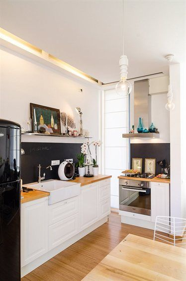 White kitchen with wooden countertops and black splashback live