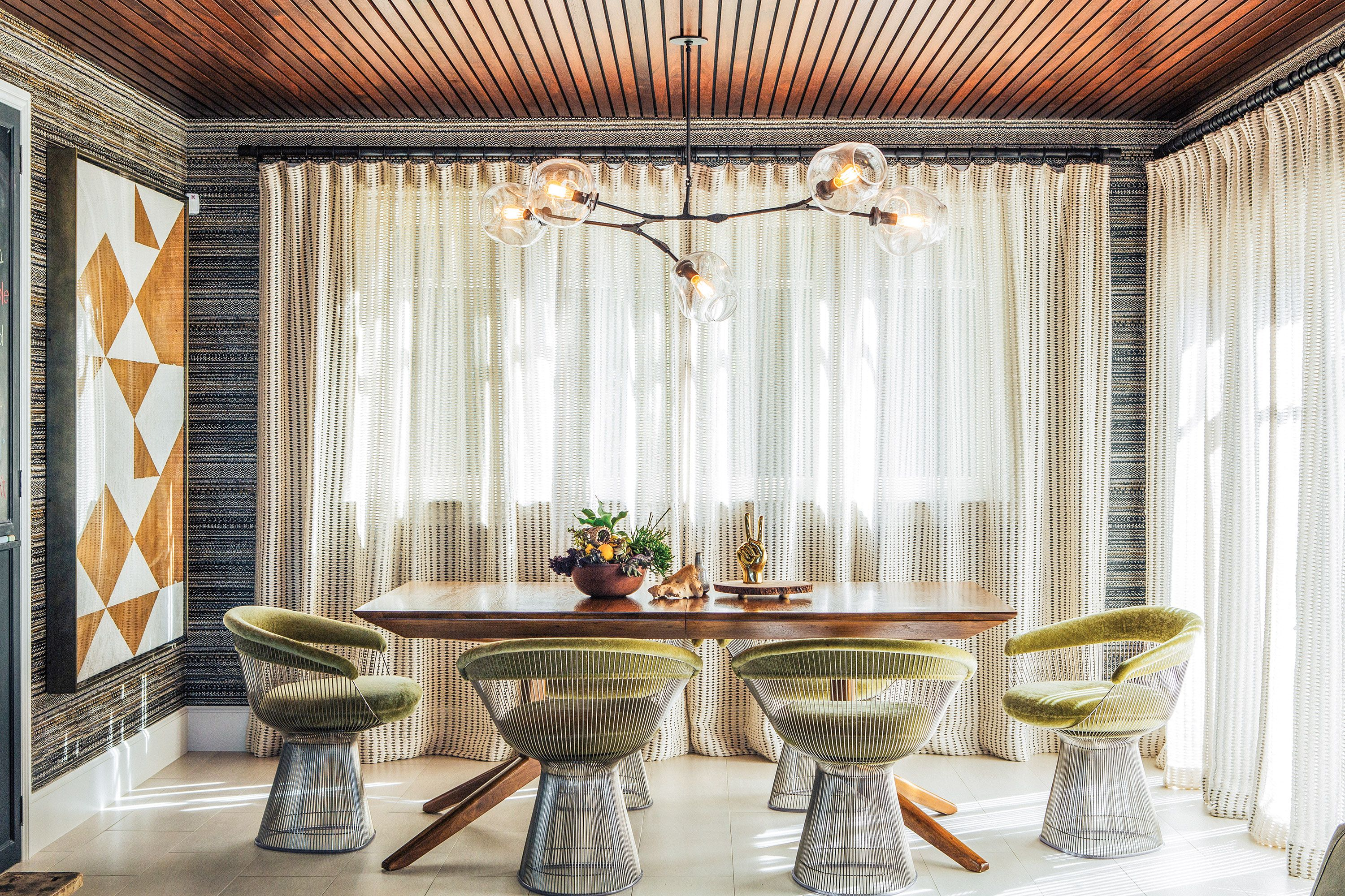 Knoll warren platner dining chairs upholstered in mohair surround a custom flo design studio table beneath a lindsey adelman brass chandelier