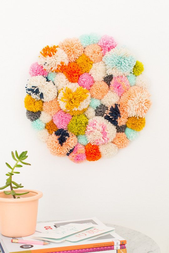 Create a cuddly wall hanging out of pom poms.