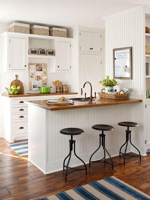 Open shelving, small scale cabinets, and a slender pantry work together to create an efficient galley kitchen featuring a two-burner cooktop and a sink. Baskets hold bulk items and take advantage of the extra space near the ceiling, while boxes above the cooktop contain dish towels and napkins.