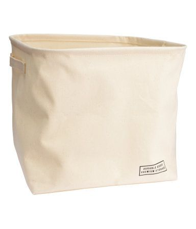 Storage basket in thick cotton twill with two handles. Concealed metal rim at top for stability and plastic coating on inside. Size 10 1/2 x 10 1/2 x 10 1/2 in.