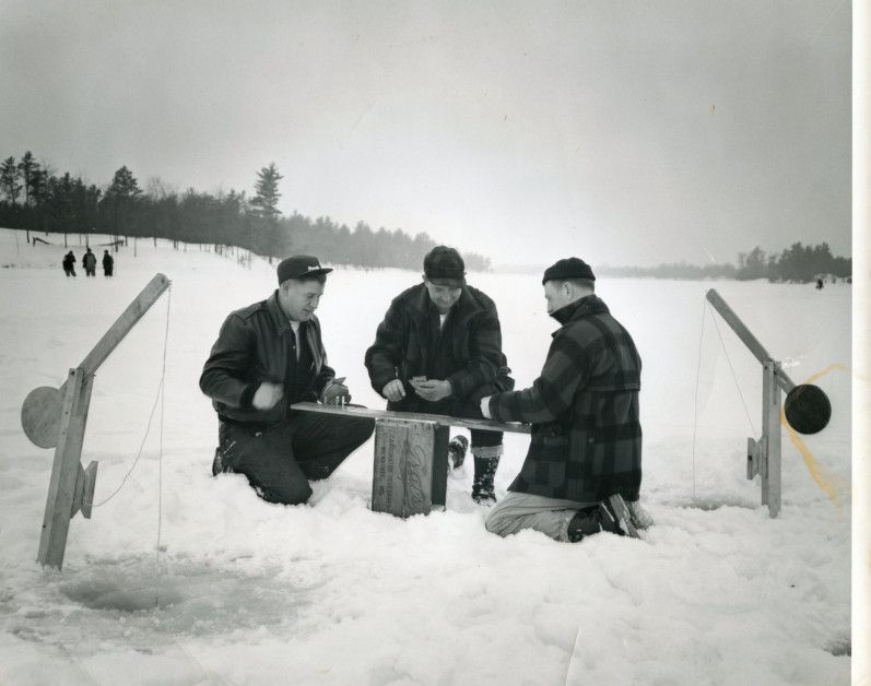 Three men play cards while ice fishing, Wisconsin Rapids ...