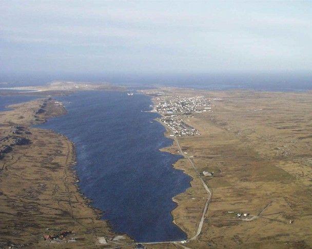 Vista aérea de la Bahía de Puerto Argentino Desde Moody Brook, a la derecha Puerto Argentino y al fondo el viejo Aeropuerto. A la izquierda, Wireless Ridge,lugar que ocupó el Reg. 7 de La Plata durante la Guerra de Malvinas