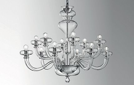 BOHEME L12 - This classic chandelier is an example  of true craftmanship . Intricate yet sleek glass- work comprises the unique  frame of the Boheme chandelier  from the central metal and hand made glass bowls , cleanly curving  arms  polished chrome structure.  An even larger size  chandelier : Boheme L8 is available.   Available in 3 color glass:  Clear, grey and black.