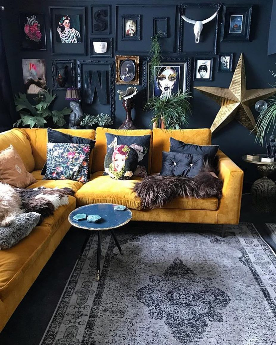 green couch, white walls, navy accent wall and mustard throw