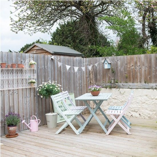 Outdoor space with decking and pastel painted table and ...