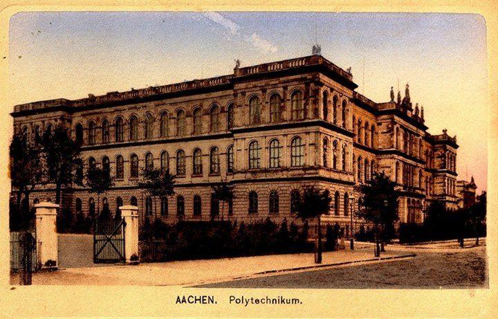 """Eine Postkarte, die das Hauptgebäude zeigt. Sie wurde am 26.2.1919 verfasst, der Text ist in französischer Sprache geschrieben und an """"Gustave"""" gerichtet.  Die RWTH wurde 1870 als Rheinisch-Westfälische Polytechnische Schule gegründet, ca. 10 Jahre später wurde sie dann in die Rheinisch-Westfälische Technische Hochschule umbenannt. Quelle: Hochschularchiv"""