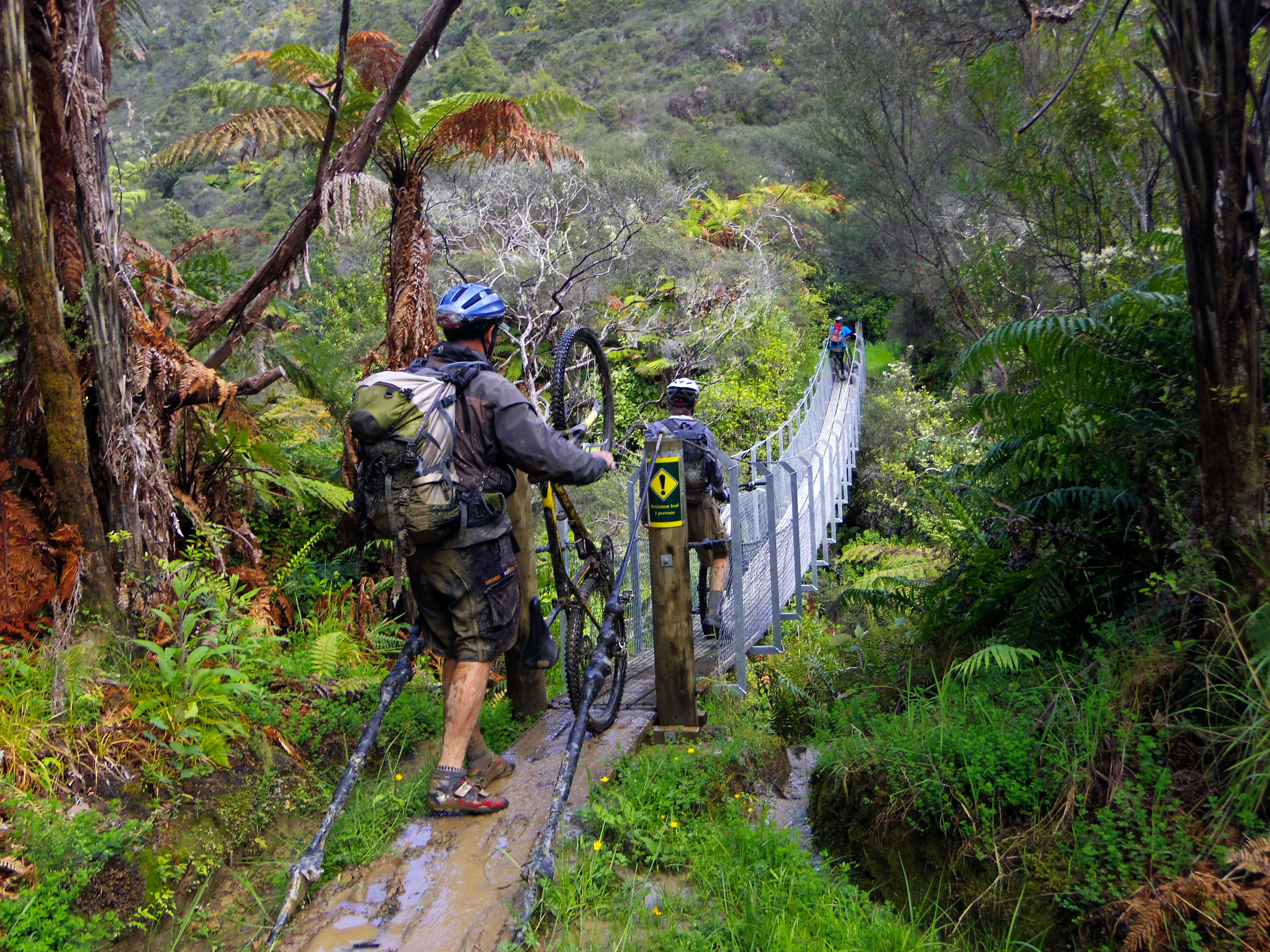 Bikers cross one of the many bridges on the Mangapurua Track in Whanganui National Park on the North Island. The trail is part of the New Zealand Cycle Trail network.