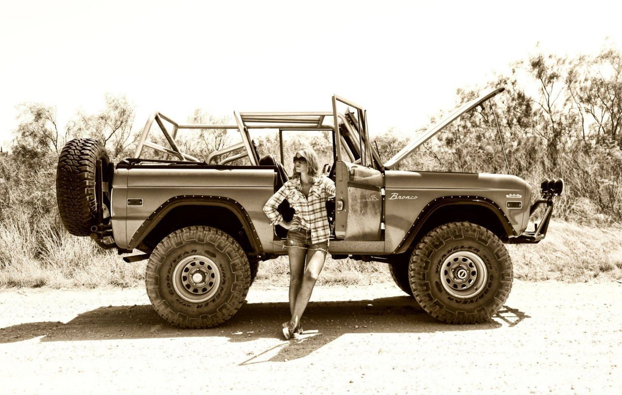 Ford bronco girl a hot country girl wearing striped shirt standing next to a ford bronco suv pimped up modified for off road in a sexy pose hot girls and