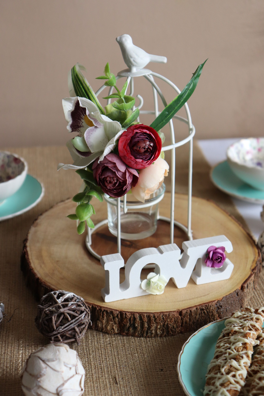 Birdcage candle holder centerpiece with floral arrangement