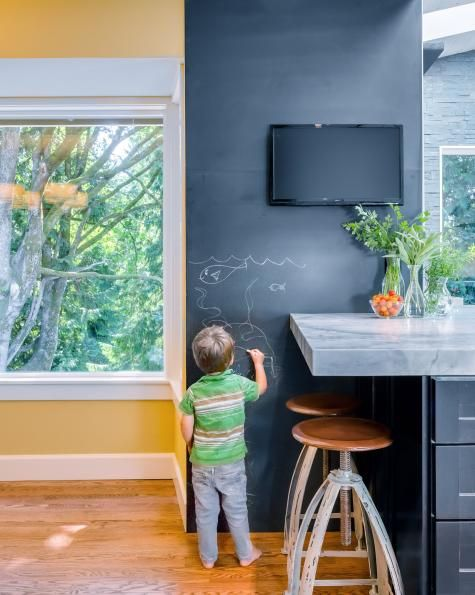 Writing grocery lists or recipes and keeping kids entertained is easy in this kitchen thanks to this reclaimed slate wall, which was fabricated into three panels and professionally installed. The color complements the contemporary space's neutral palette while serving as a fun focal point.