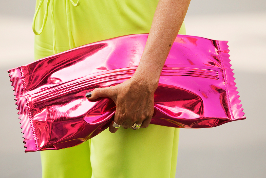 A vibrant pink Margiela for H&M clutch that resembles a giant candy wrappe