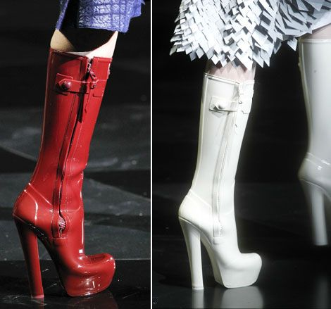 More Details Jimmy Choo Edith Rubber Knee-High Rain Boot Details Jimmy Choo knee-high rubber boot with star top studs. Stacked heel with platform and studding. Round patent leather capped toe. Pull-tabs at top collar. Pull-on style. Padded footbed. Rubber .