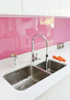 pink-splash ..  I'm actually considering doing this in my new house ... with white.  By painting the backside of glass and attaching to wall you get a very high gloss.  Chic! ~ Sandy M
