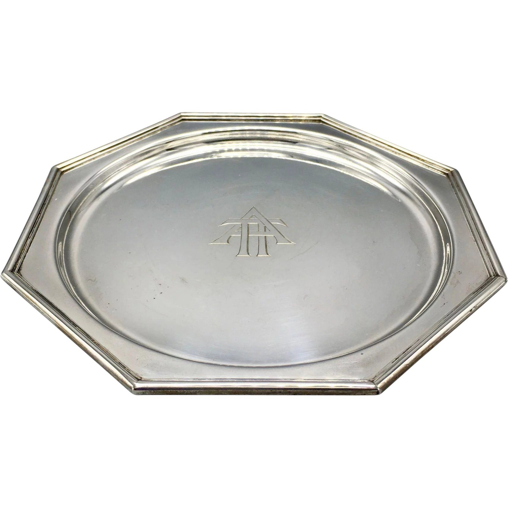 Antique J E  Caldwell Sterling Silver Art Deco Plate 6  is part of Silver Home Accessories Art Deco - A beautiful antique Art Deco sterling silver plate J E  Caldwell & Company of Philadelphia  There is a monogram 'ATT' in the center of the plate  The plate is marked 'J E  Caldwell & Company of Philadelphia' and '925 Sterling 1000 ' There is also an engraved name and a date on the back side 'Phyllis Douglas Cochran, Feb 19, 1927 ' The plate is in a very good condition  No dents, damage or repairs  It features the typical Art Deco geometric forms   A great finding for a J E  Caldwell collector or an admirer of antique silver   Measurements  The plate weighs 4 81 troy ounces (ozt) or 149 7 grams    Dimensions 6  x 6  The origins of J E  Caldwell jewelry date back to 1839, when watchmaker James Emmott Caldwell opened the doors of his Philadelphia wearable arts emporium  His target audience was always the wealthy Philadelphia jewelry buyer who had a penchant for the flair of Europeanstyle jewels  In the course of time, Caldwell added silver and objets d'art to his lineup of goods  It took the Caldwell name a few changes in location and of management to get established in the city  In 1868, the Caldwell location at 902 Chestnut Street was established  When the Art Nouveau fashion gripped the United States by the end of the 19th century, Caldwell's artisans were instrumental in setting a tone for the trend  Their handmade pieces were considered by many the definitive jewels of the period  In keeping with the Art Nouveau style, the motifs include examples of flora and objects rich in curvatures  Moving the store to the corner of Juniper and Chestnut in 1916, the Caldwell firm next tackled the Art Deco craze  Once again, the artisans embraced the new style and put their own spins on it  The result was a reputation for superior Art Deco jewelry that not only cemented the company's name at the time but keeps making it famous to this day