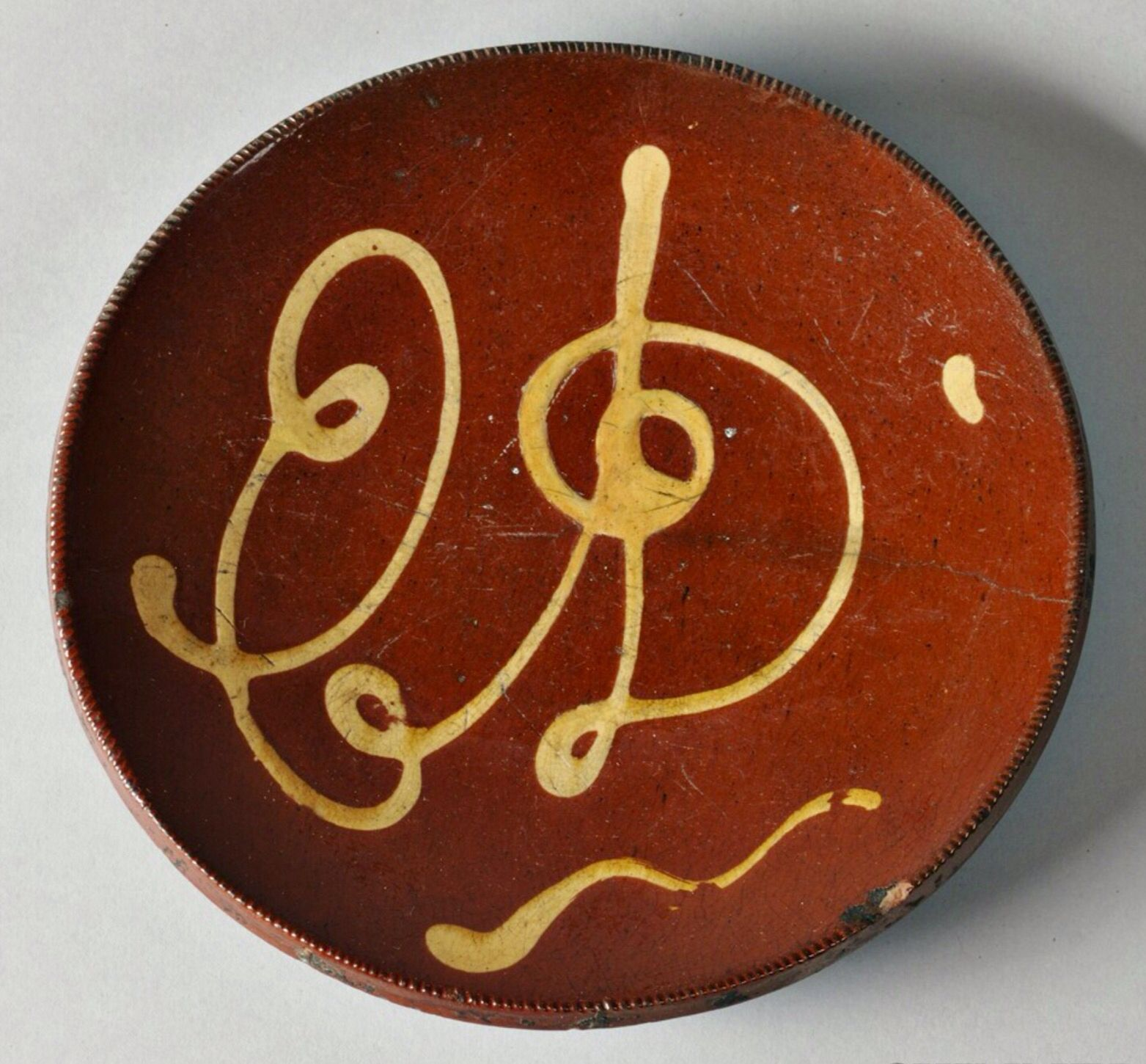 """Skinner's - The Personal Collection of Lewis Scranton, Auction 2897M. May 21, 2016. Lot: 230.  Estimate: $400-600.  Realized: $425.   Description:  Redware Plate with Yellow Slip Inscription """"ED,"""" Norwalk, Connecticut, early 19th century, round, with coggled rim, (hairline crack, minor rim chips), dia. 8 1/4 in."""