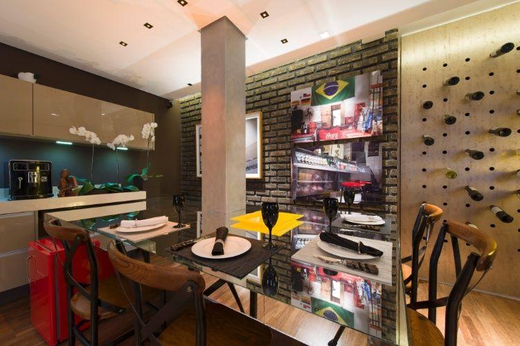 Inspirado em lofts, Gustavo Paschoalim desenhou a Sala de Vinhos. Na área de jantar, o destaque fica por conta dos tijolos aparentes e da parede com furos para armazenar as garrafas. A 27ª Casa Cor SP
