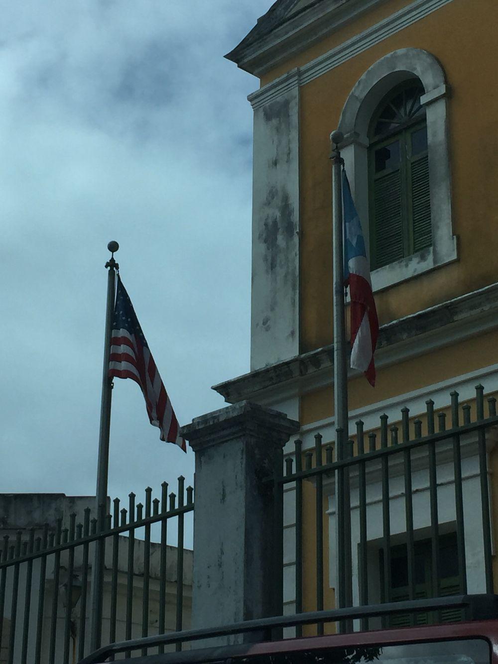 Escuela de Artes Plásticas cumple con reglamentación de banderas. En buenas condiciones, izadas al mismo nivel en astas y la bandera de PR a la derecha del observador. Tomada lunes 7 de marzo 2016 a las 10:23am  #banderasyescudosVSJ #sagradoenero2016