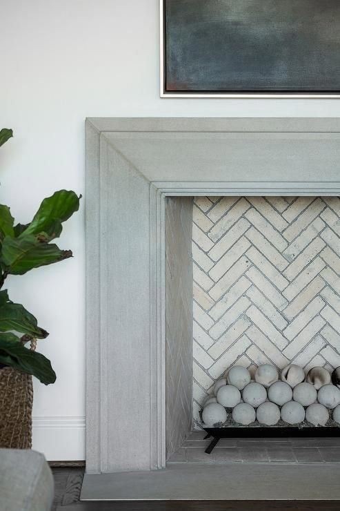 Beneath a framed TV niche, a gray beveled mantel frames a fireplace fitted with an ivory herringbone firebox and concrete fire balls. #fireplacedecorationsimages