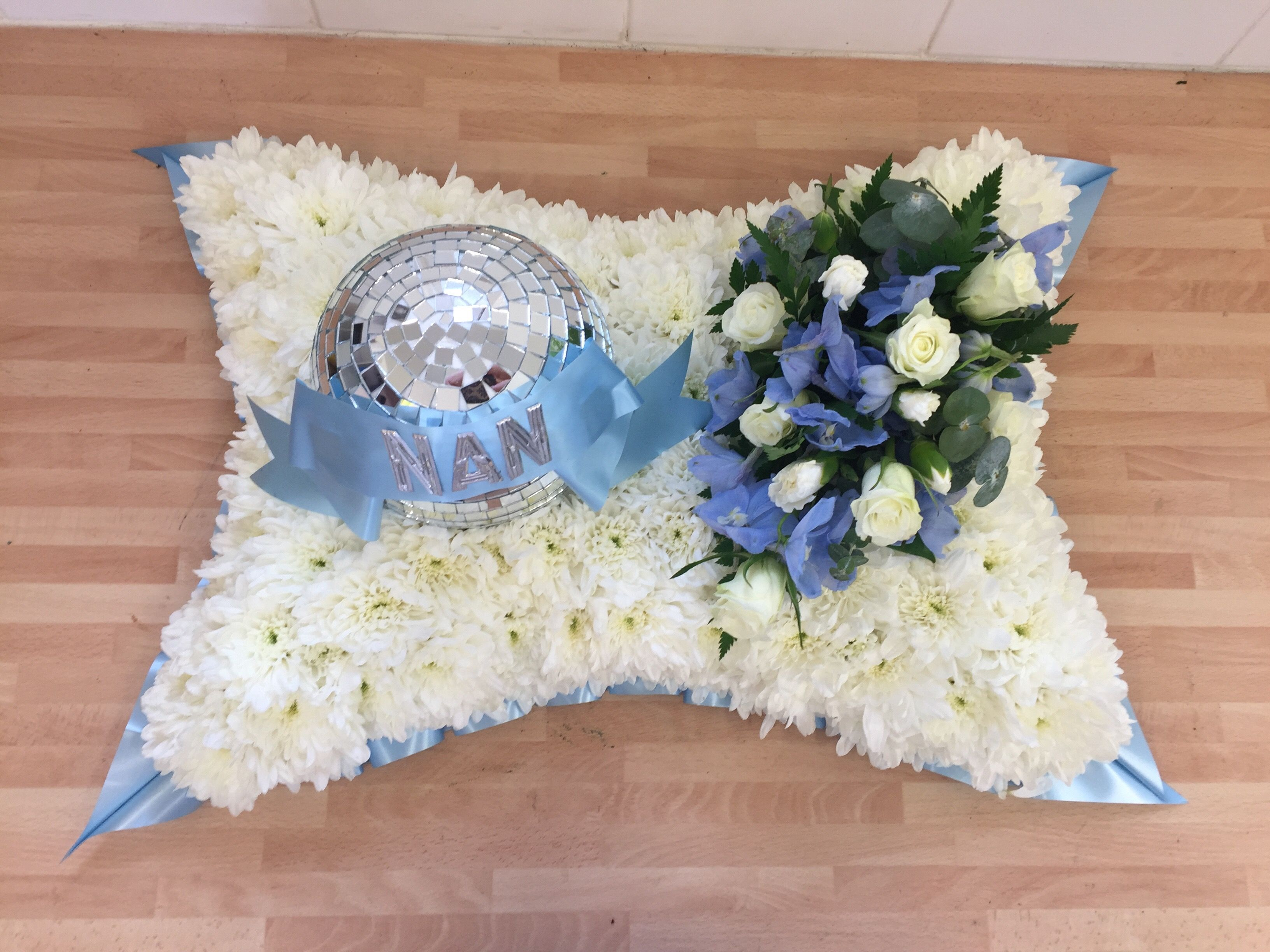 White Based Cushion Funeral Tribute With Baby Blue Ribbon Edge