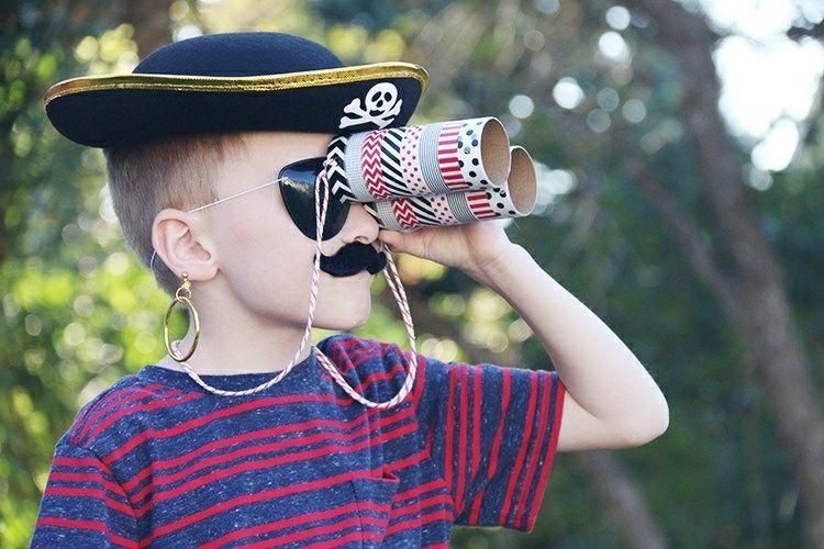 Junge mit piraten hut schwarze augenklappe und buntem fernglas