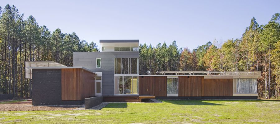 The central space where the three bars meet, with a highest point of 22 feet, has a kitchen, dining, and living spaces and is open to the second story and continuous balcony above. Visual connections are the essence of the house, which boasts a combination of storefront floor-to-ceiling and aluminum-framed operable and non-operable windows.