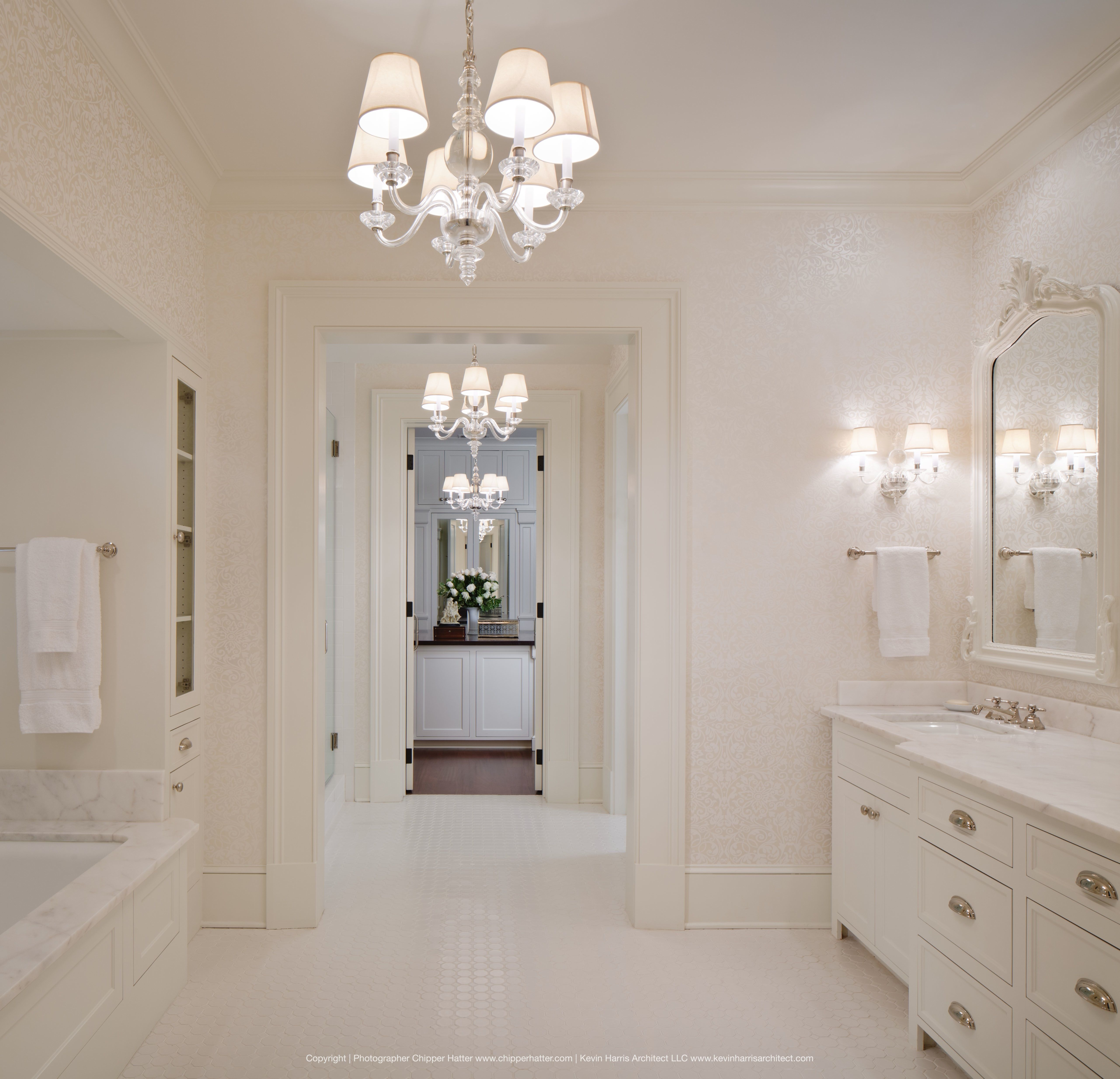 Lots Of Natural Light In Bright White Bathroom With Tile Floors And Clear Acrylic Chandeliers