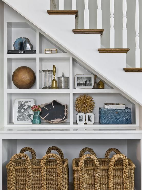 Under A Transitional Staircase Is An Alcove Fitted With Built In Shelves And A Pair Of Seagrass Bask Transitional Decor Bedroom Staircase Shelves Stair Shelves
