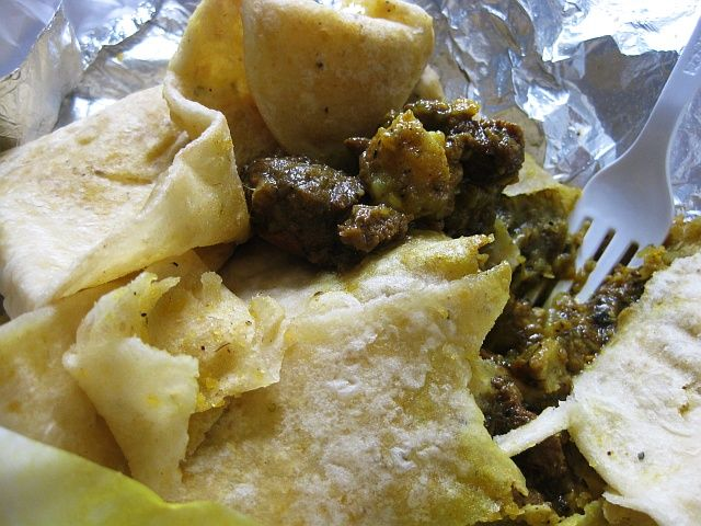Digging Into A Curry Goat And Potato Roti Curry Goat Trini Food Caribbean Recipes