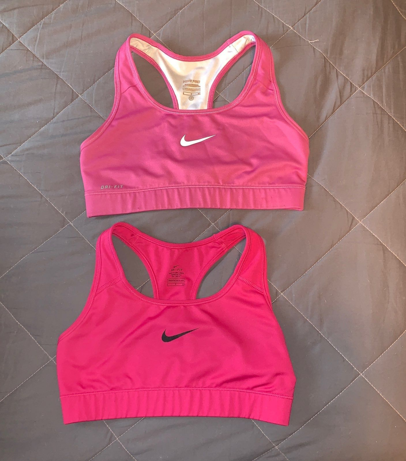 One hot pink, one light pink Nike Sports bra. Both in