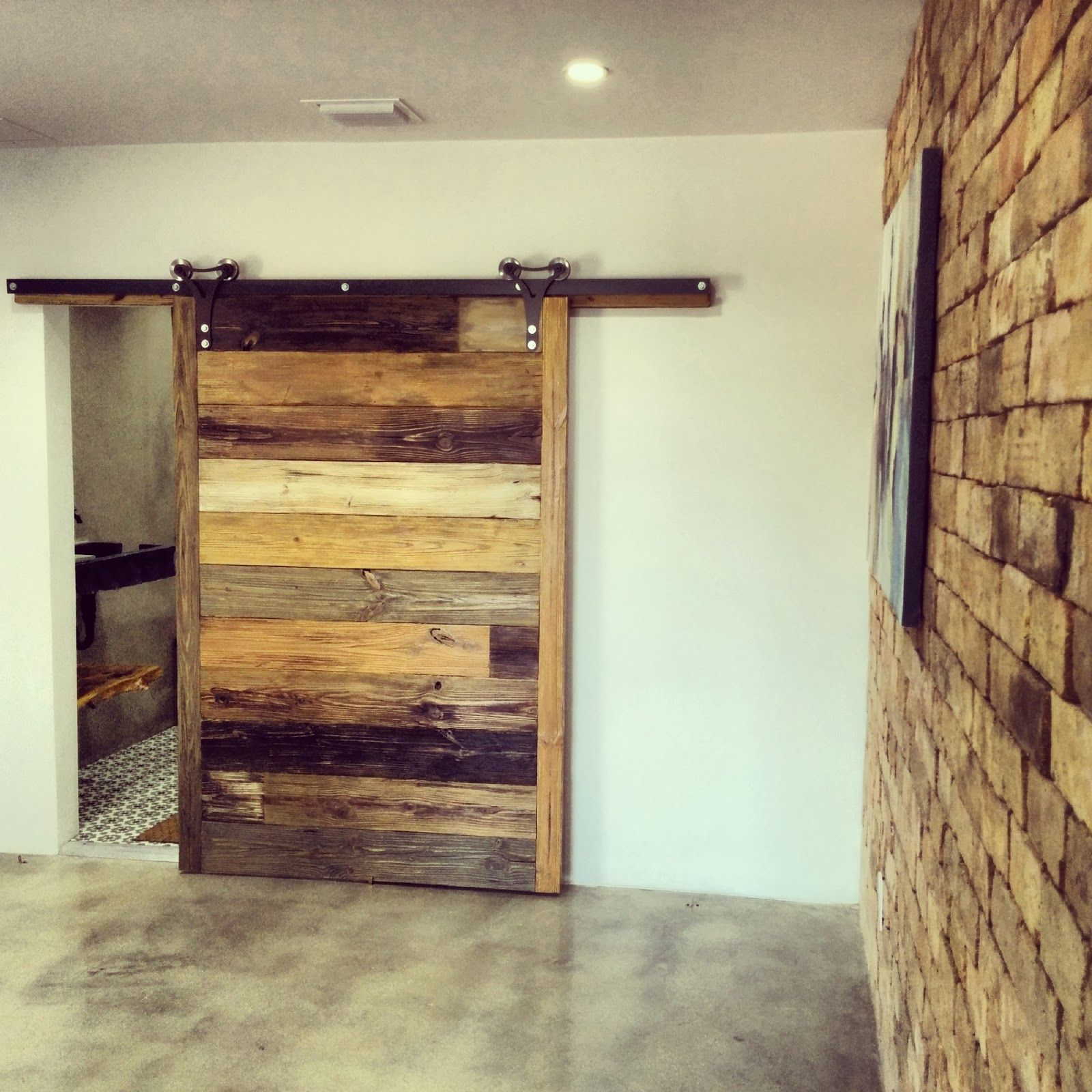 Amazing large single sliding barn door with brick wall for Wood barn homes