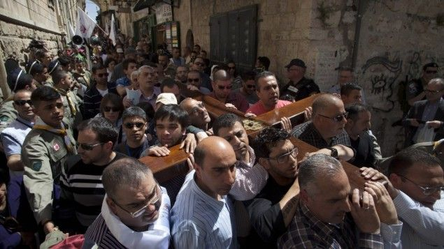 Christian worshippers carry a cross towards the Church of the Holy Sepulchre, traditionally believed by many to be the site of the crucifixion of Jesus Christ, during the Good Friday procession in Jerusalem's Old City, Friday, March 29, 2013. (AP Photo/Sebastian Scheiner)