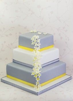 Aria is a stylish 3 tier square cake in modern grey and white, complimented by yellow ribbon and white hydrangeas.