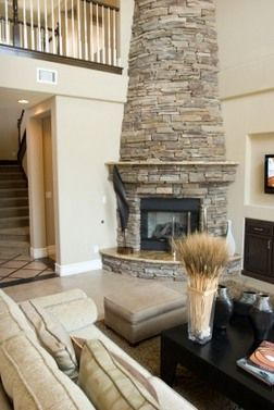 Modern Room With High Ceiling Round Corner Fireplace Stacked Stone Chimeneas Manteles