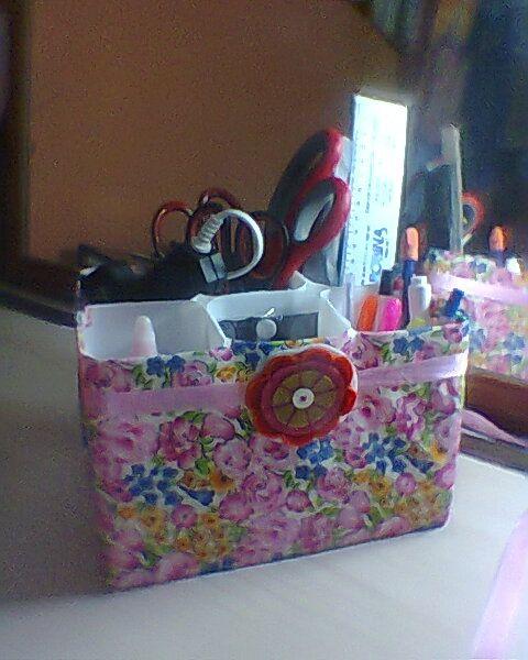 organizador de escritorio, elaborado con botellas de yogurt, forrado con tela y decorado con cinta y una flor de fieltro
