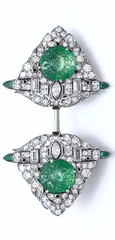 AN ART DECO EMERALD AND DIAMOND JABOT PIN, BY MARCUS & CO. - Each terminal set with a carved cabochon emerald, within a circular, baguette and marquise-cut diamond pierced openwork shield-shaped plaque, accented by cabochon onyx and triangular-shaped cabochon emeralds, mounted in platinum, (may also be worn as a pair of clips), circa 1920.
