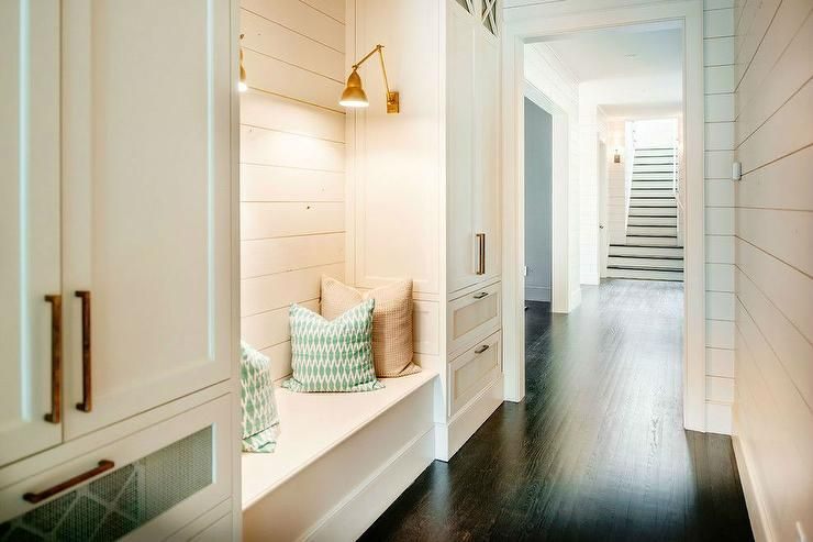 Long mudroom boasts walls clad in shiplap lined with a built-in