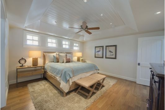 Coastal bedroom design with unique ceiling design, end tables, and decor.