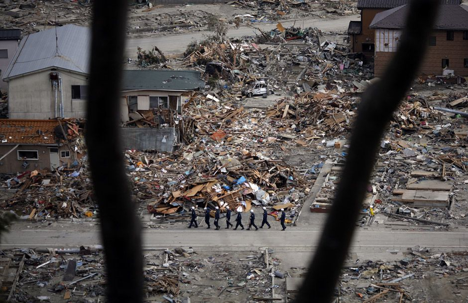 Members of a search and rescue team walk in an area destroyed by the March 11 earthquake and tsunami in Ishinomaki, northern Japan April 4, 2011. REUTERS/Carlos Barria