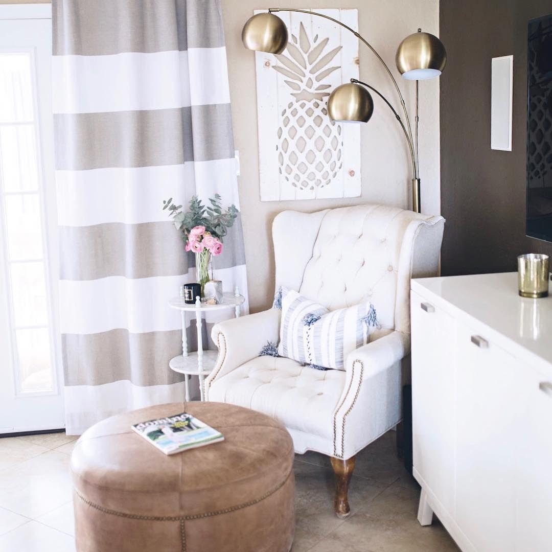 A vintage, linen armchair and an brass arc floor lamp