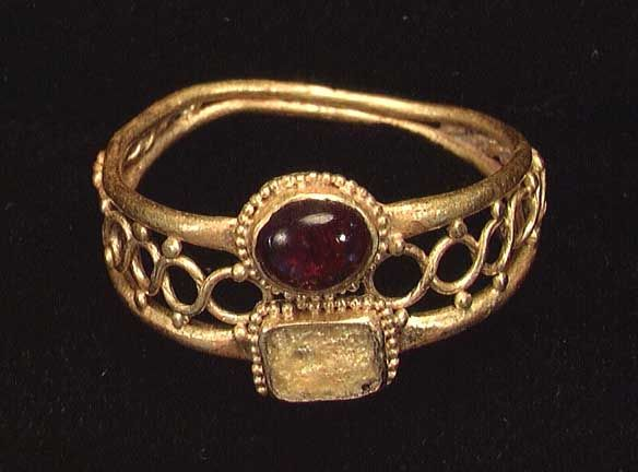 A ROMAN GOLD RING, ca. 4th century AD. The ring set with two settings, one a cabachon garnet.