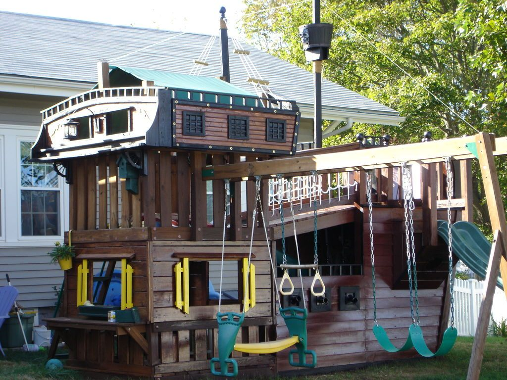 cool pirate ship playhouse with green swing and slide backyard
