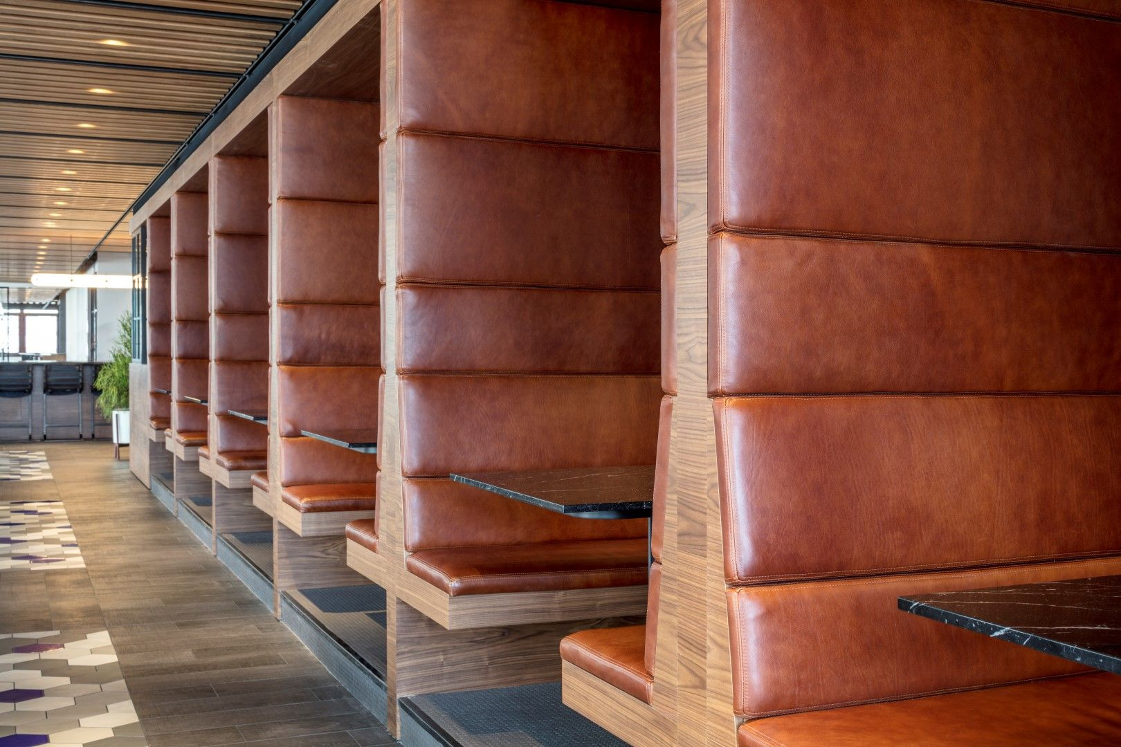 Fully upholstered leather boothsbanquettes with marble tables and fully upholstered leather boothsbanquettes with marble tables and penny tile floors oak slat dailygadgetfo Image collections