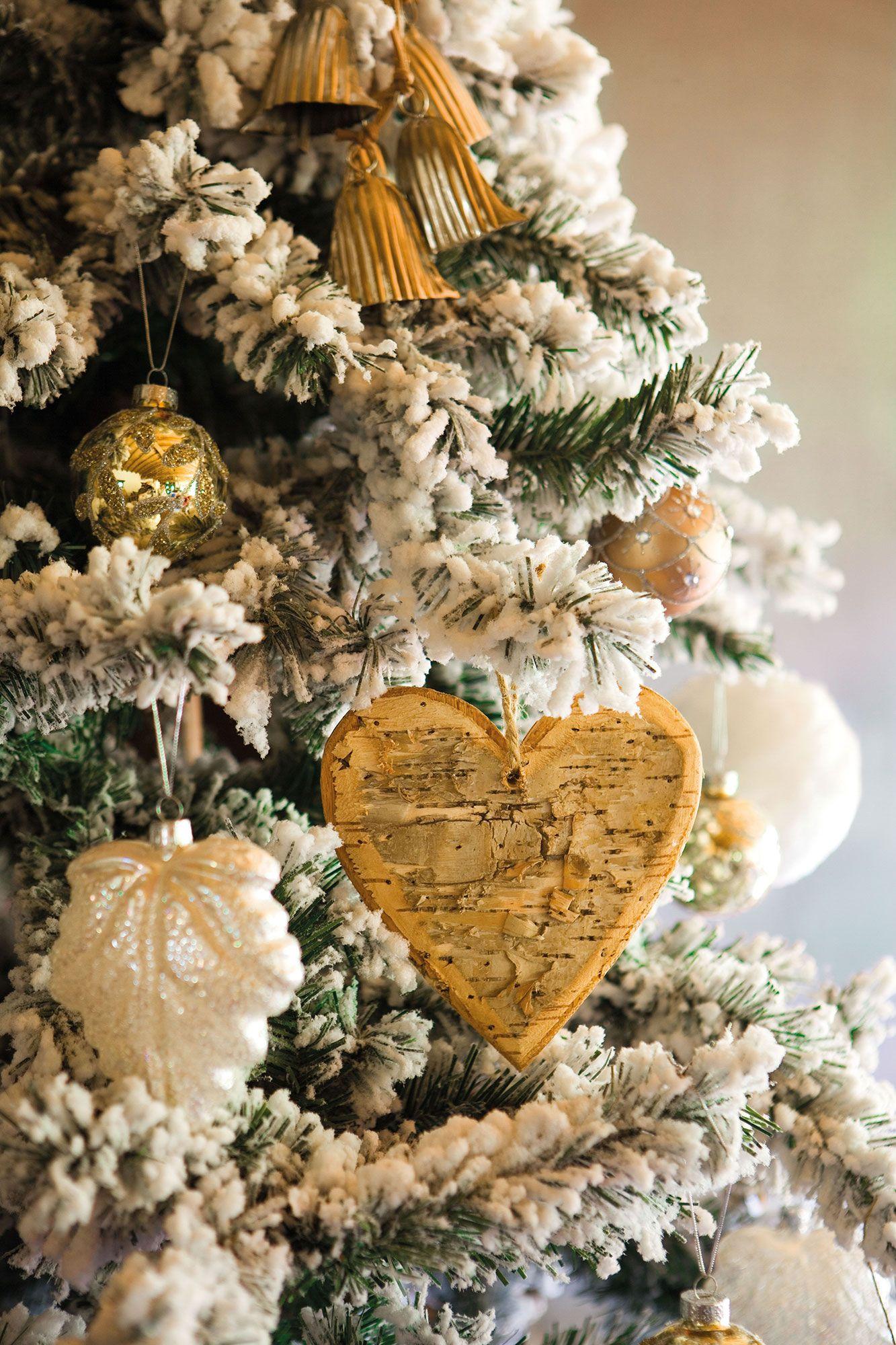 Detalle de adornos navide os en blanco y dorado en rbol nevado