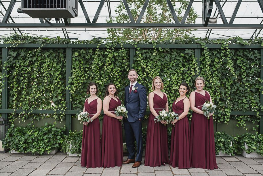 24d7d3c031ba Groom in a navy suit with wine colored long neck tie. Bridesmaids in wine  colored floor length flowy bridesmaid dresses with a beaded belt.