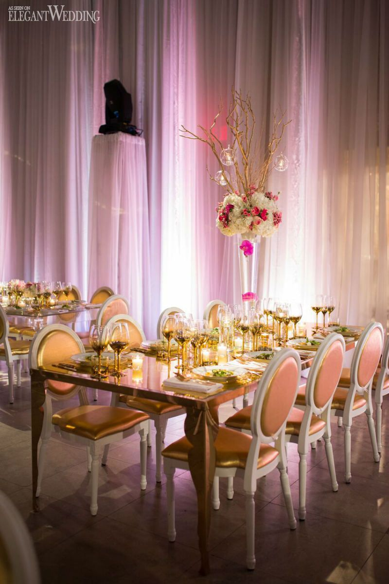 gold table setting with pink floral centrepieces for a